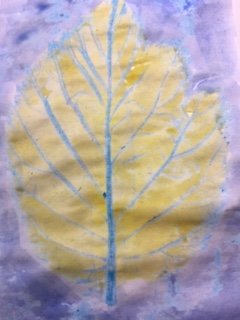 A crayon rubbing of a leaf has been given a light colour wash with blue water paint