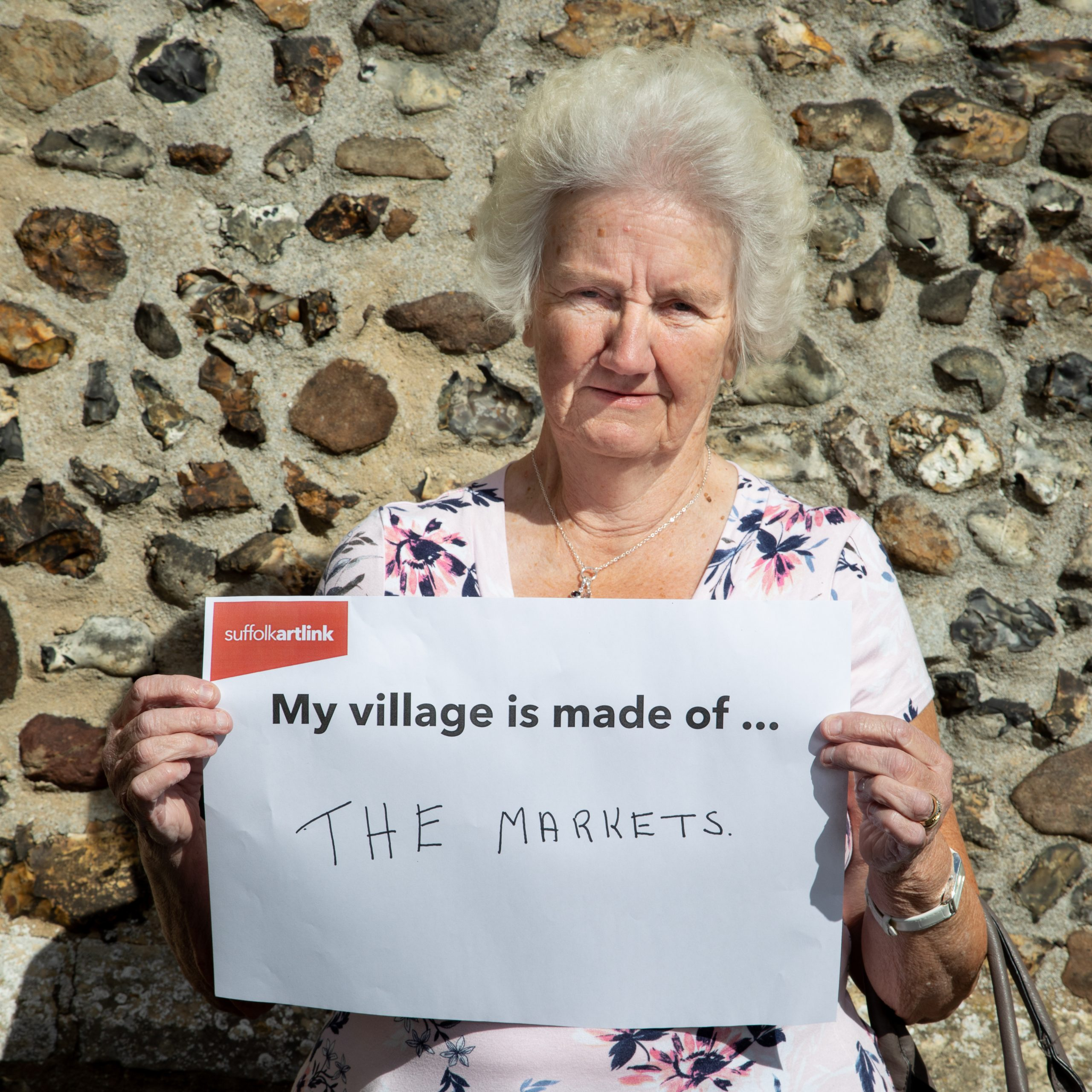 A woman holding a placard that reads My Village is made of The Markets