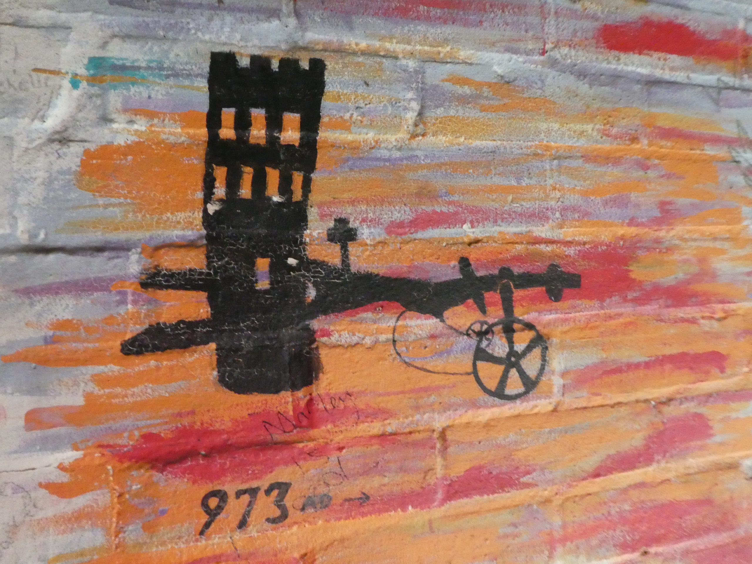 A painting of the village sign depicting a castle, an old-fashioned hand-driven plough and the date 973