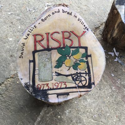 A photograph of the Risby village sign, bonded on to the top of a log of wood