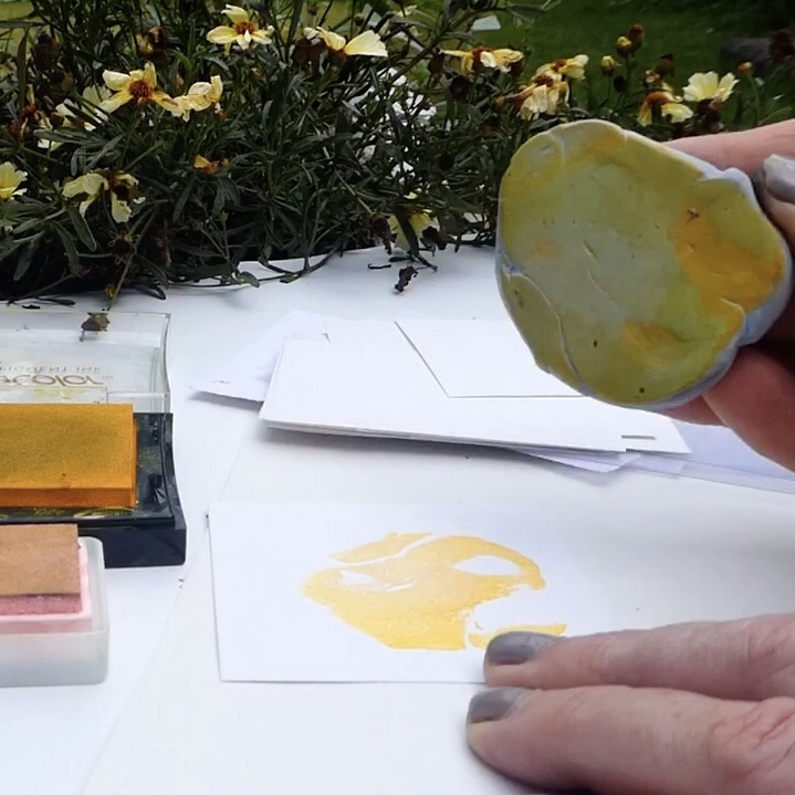 A hand holding a piece of yellow-inked Blutack over a white sheet of paper, having printed a yellow shape onto the paper