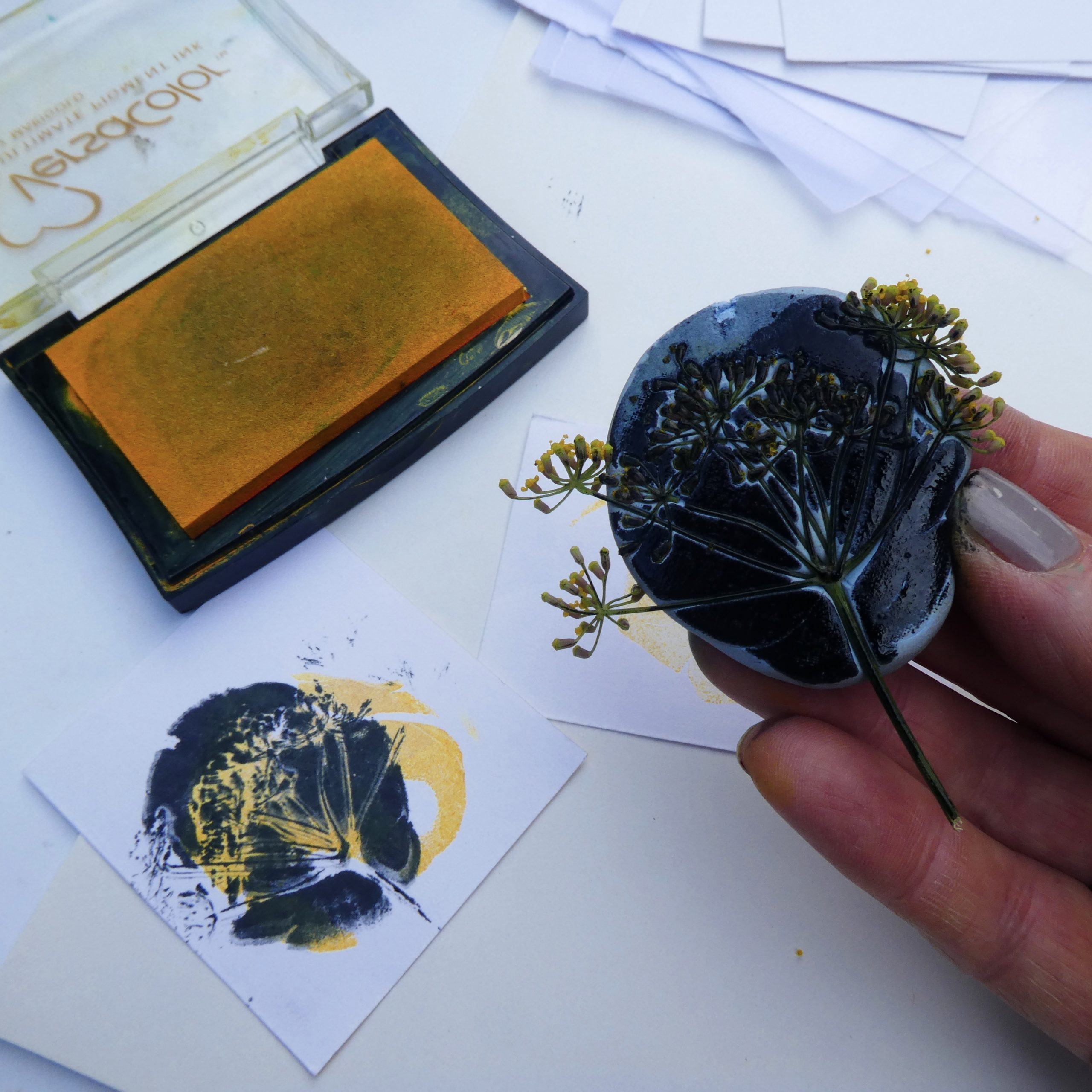 A hand holds an inked up Blutack with seed head and in front is the print made using it