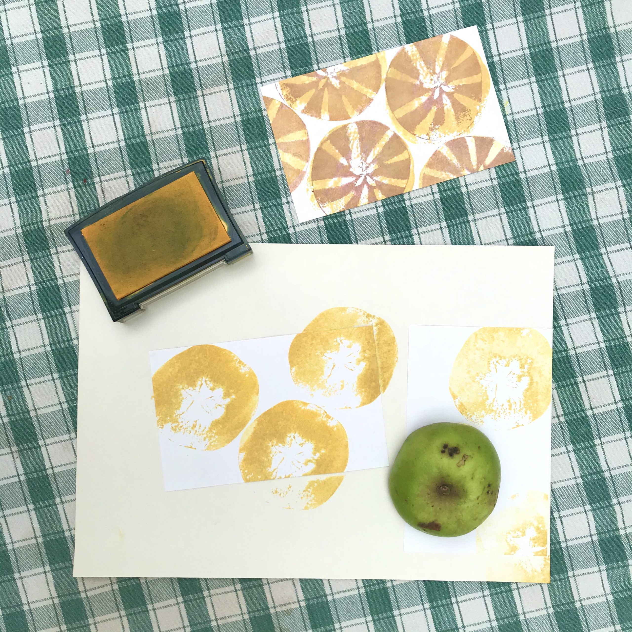 Using half an apple to print a simple shape onto the paper in yellow ink