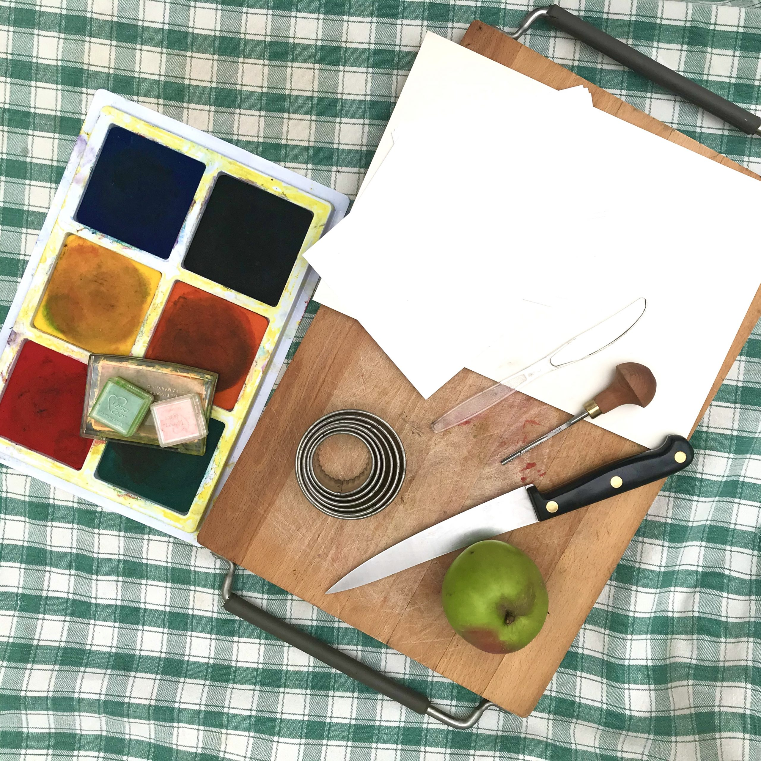 A chopping board, with apple, knife and paper, and a paint palette