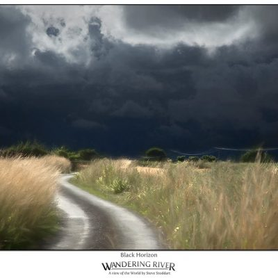 A view across fields with a stormy black sky overhead